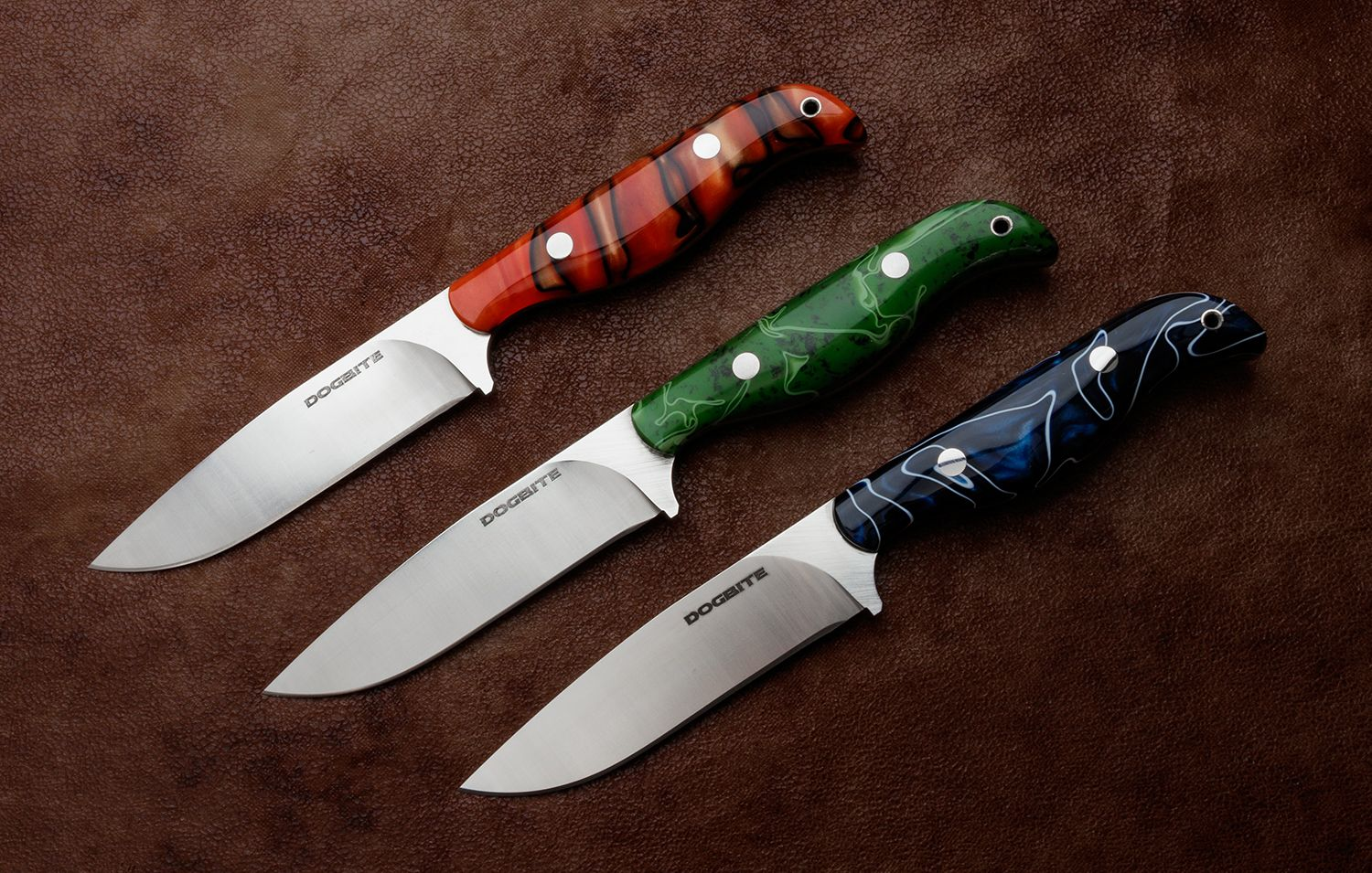 Orange, Green, and Blue Dogbite All-Around Fixed Blade Knives on leather background