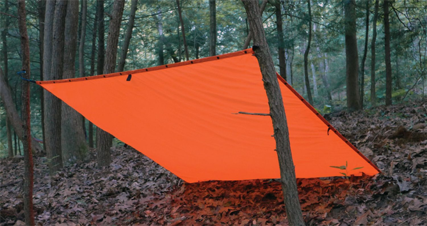 ESEE Signal Survival Tarp stretched between two trees and the ground