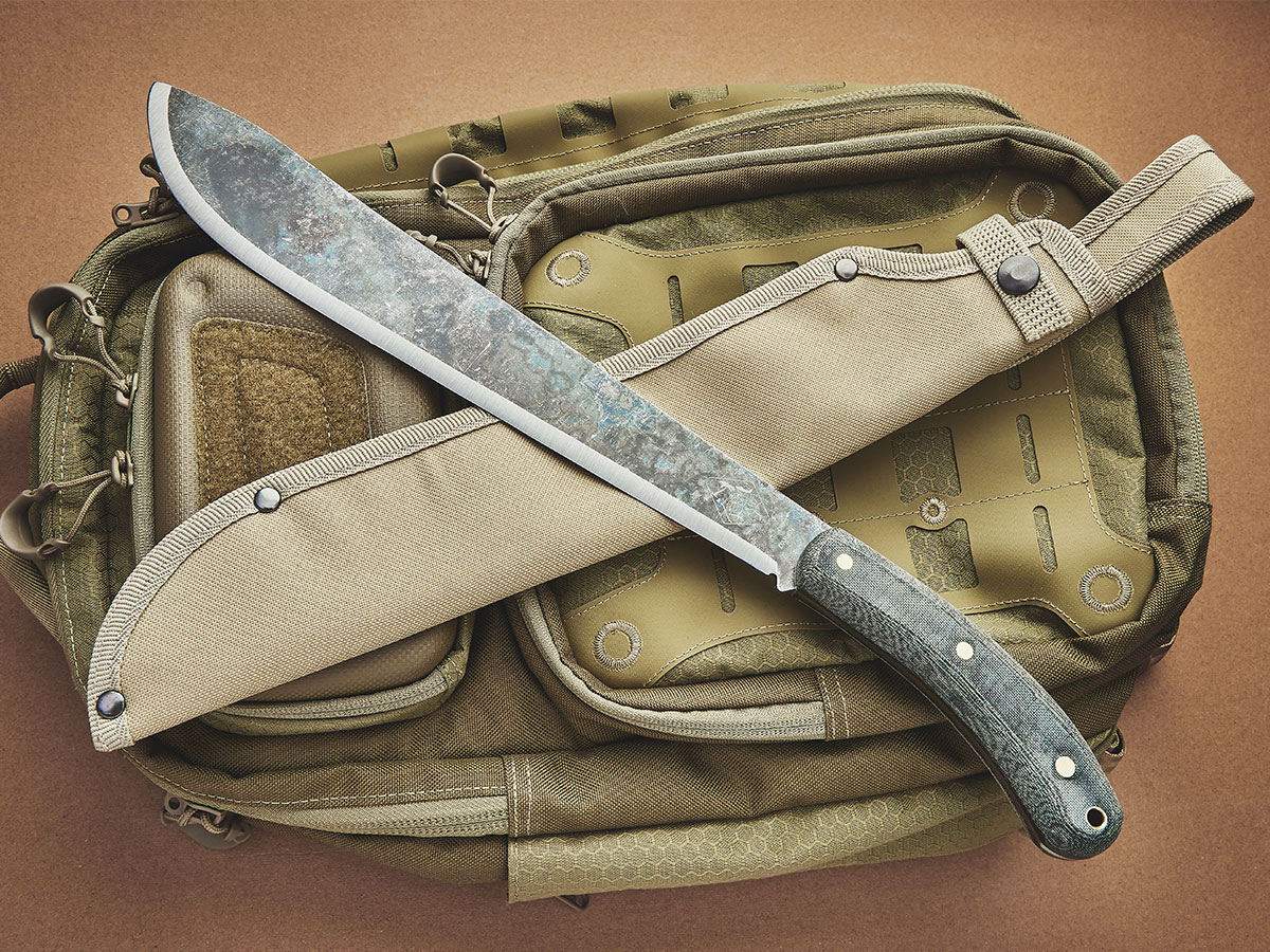 ESEE Expat Darien Machete with sheath resting on a backpack