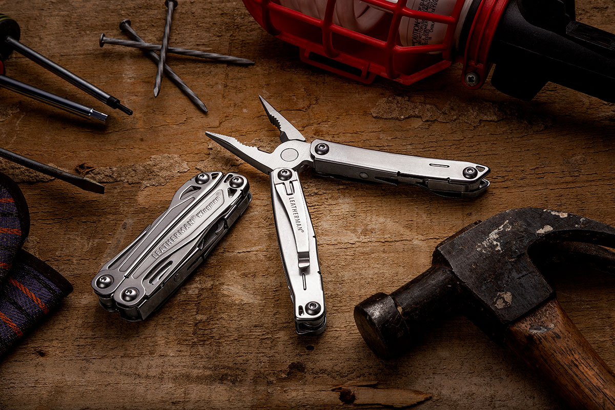 Leatherman Wingman and Sidekick on a workbench surrounded by tools and hardware