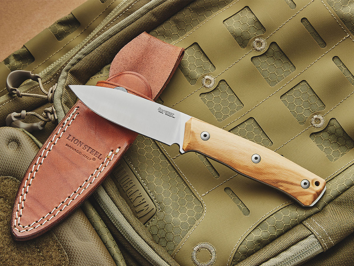 LionSteel B35 Bushcraft fixed blade and sheath resting on a backpack