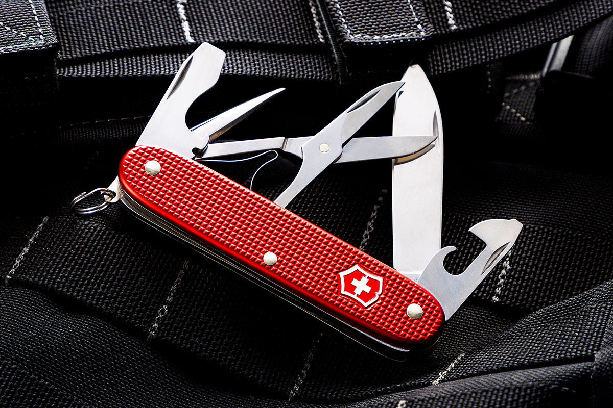 KnifeCenter Exclusive Red Alox Pioneer X Swiss Army Knife on black nylon webbing
