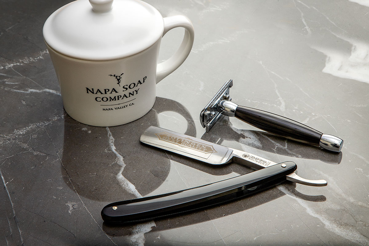 Straight razor, safety razor, and shaving mug on a marble surface