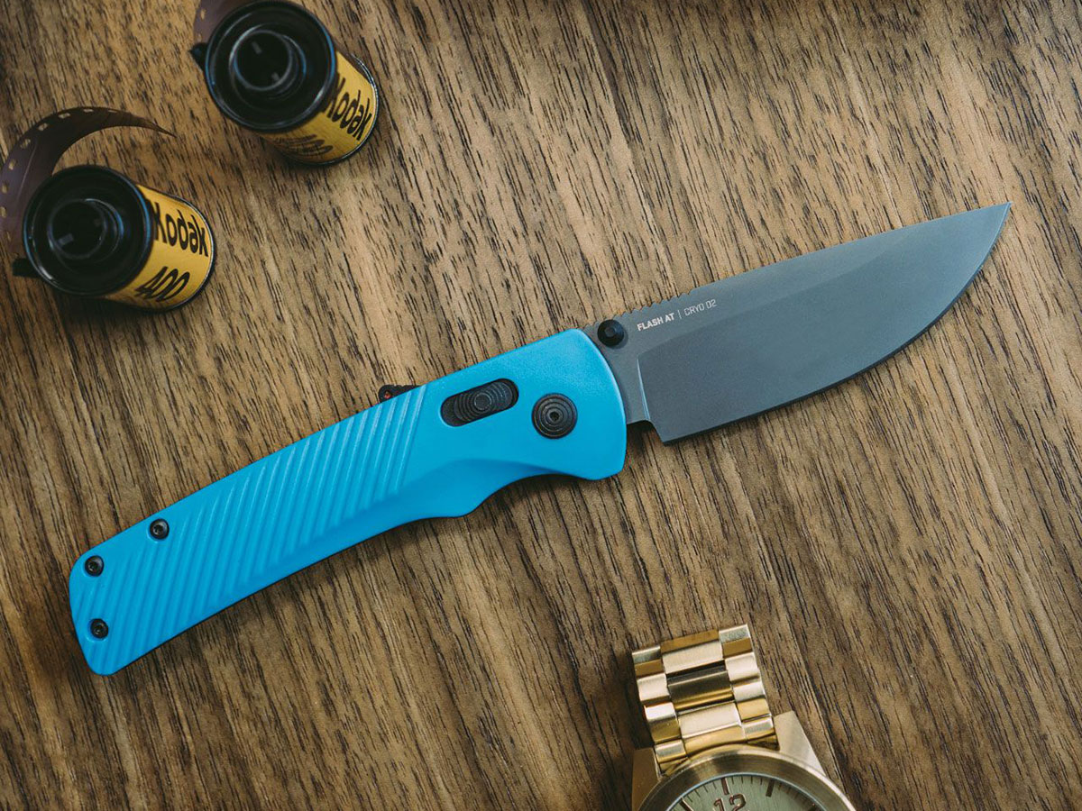 SOG Flash AT pocketknife with cyan handles on wood surface, surrounded by a gold wristwatch and 35mm film rolls