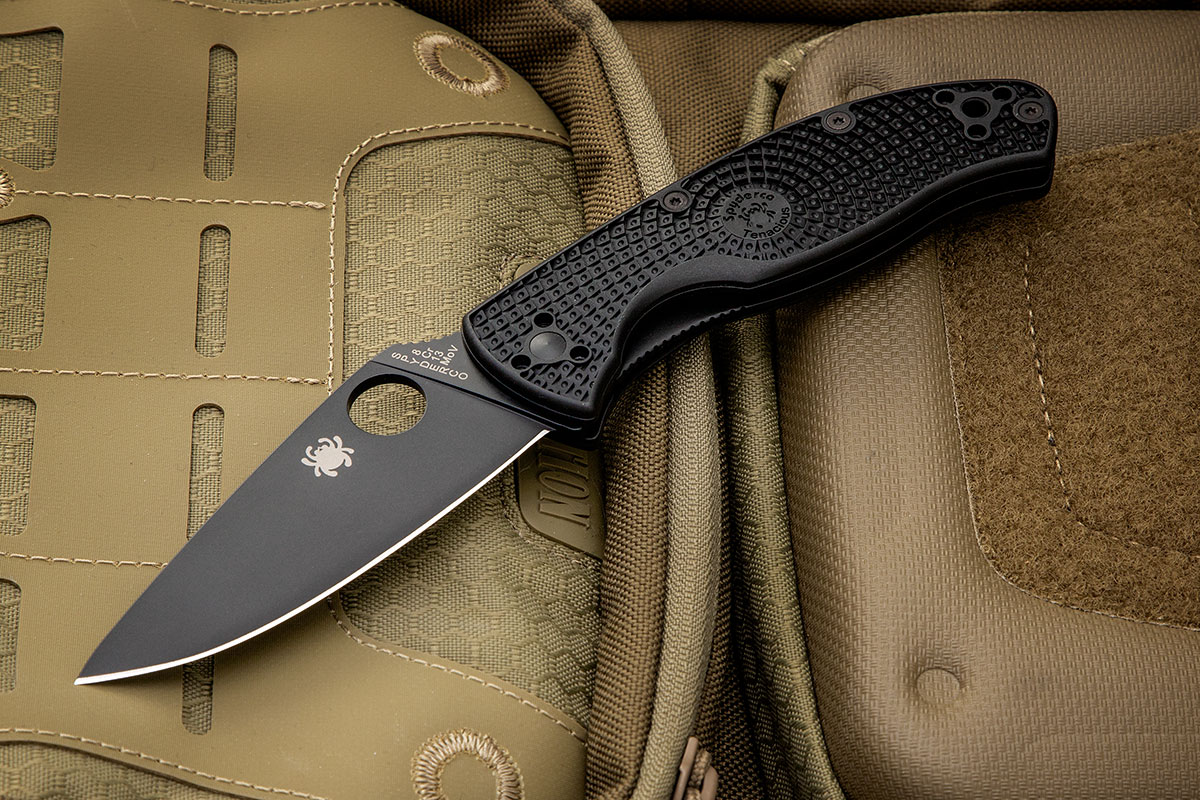 Spyderco Tenacious Lightweight with black blade on a Maxpedition pack
