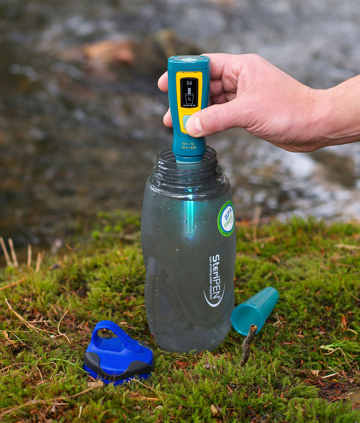 SteriPEN Ultra UV Water Purifier being used to sterilize water in a bottle next to a running stream