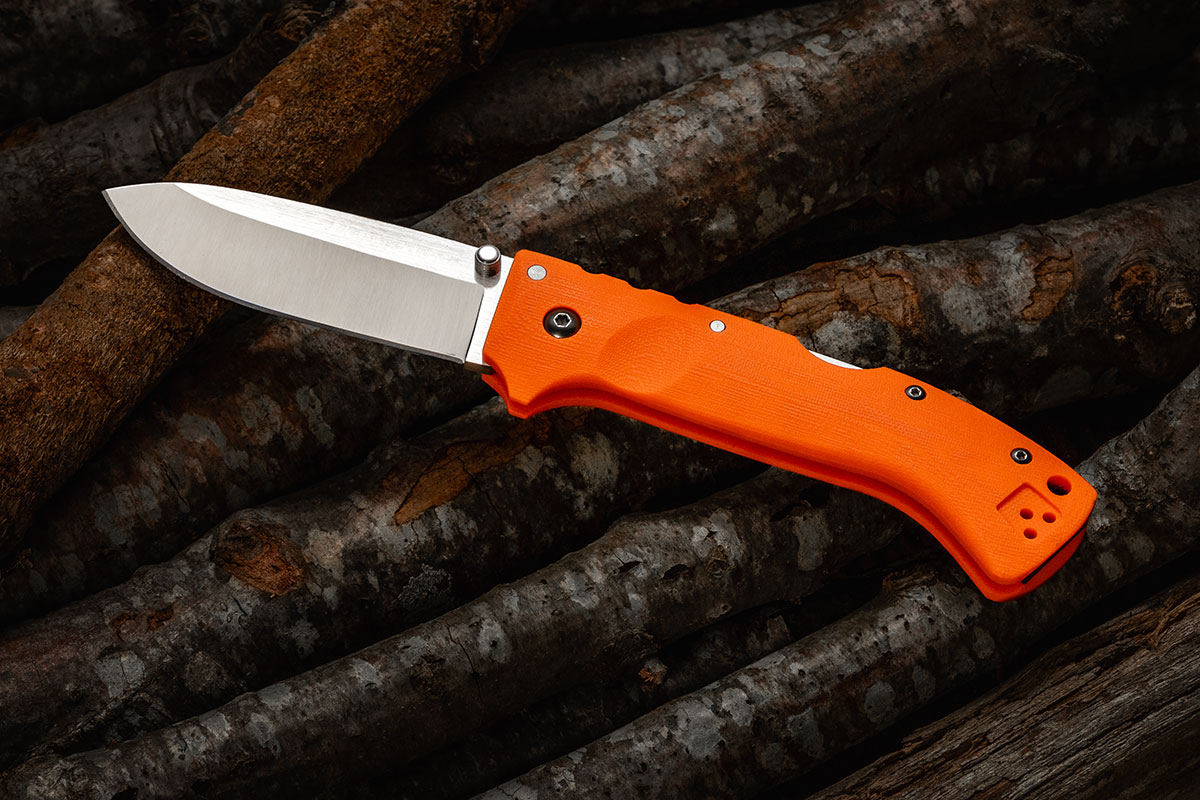 Cold Steel Ultimate Hunter with orange G10 on logs