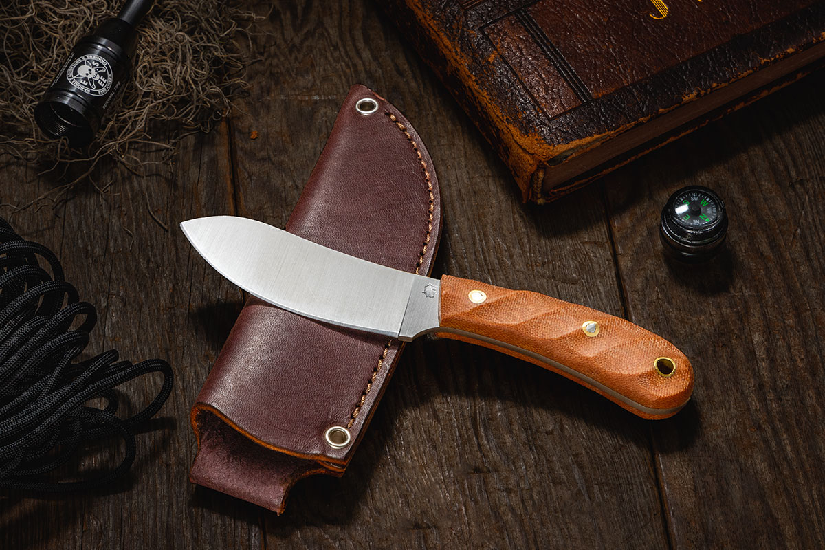 L.T. Wright Camp MUK with Twisted natural Micarta handle, resting on sheath and surrounded by small survival items