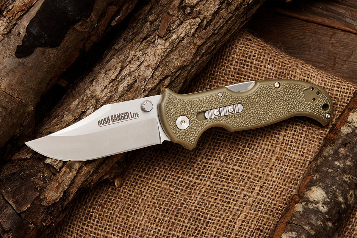 Cold Steel Bush Ranger Lite folding knife on background of logs, wood plank, and burlap