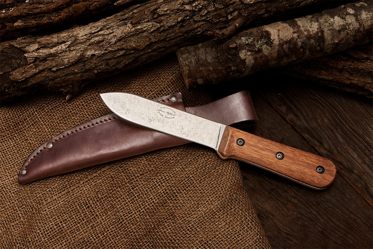 KA-BAR Becker BK62 with sheath on background of logs, wood plank, and burlap