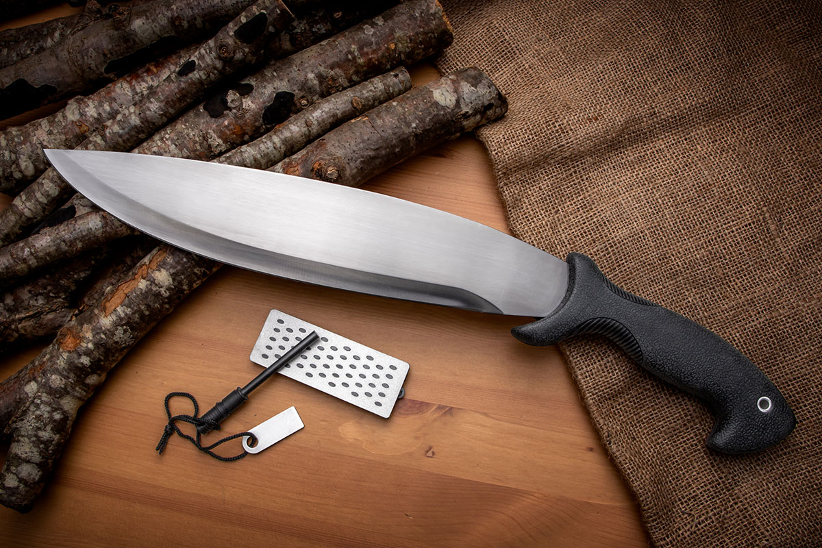 """Schrade 14"""" Bolo Machete with included sharpener and firestarter resting on burlap and wood"""