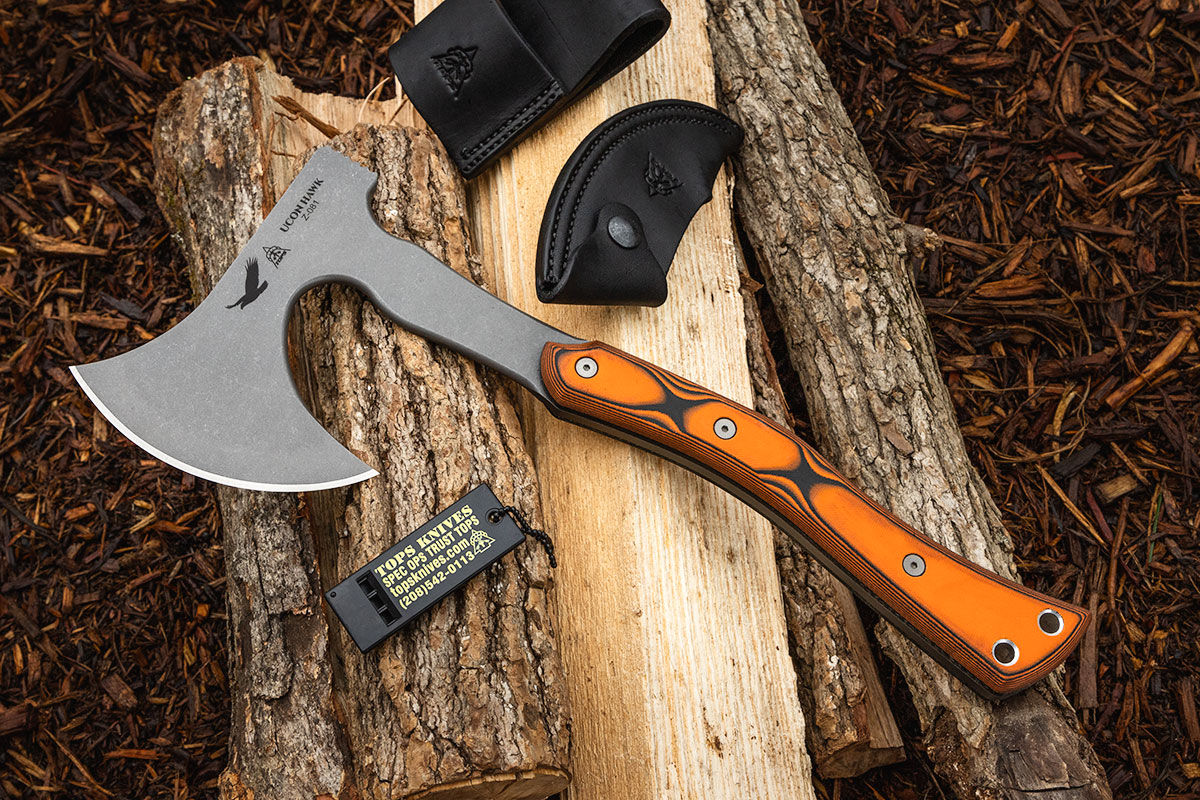 TOPS Ucon Hawk with included whistle and sheath on top of a pile of logs
