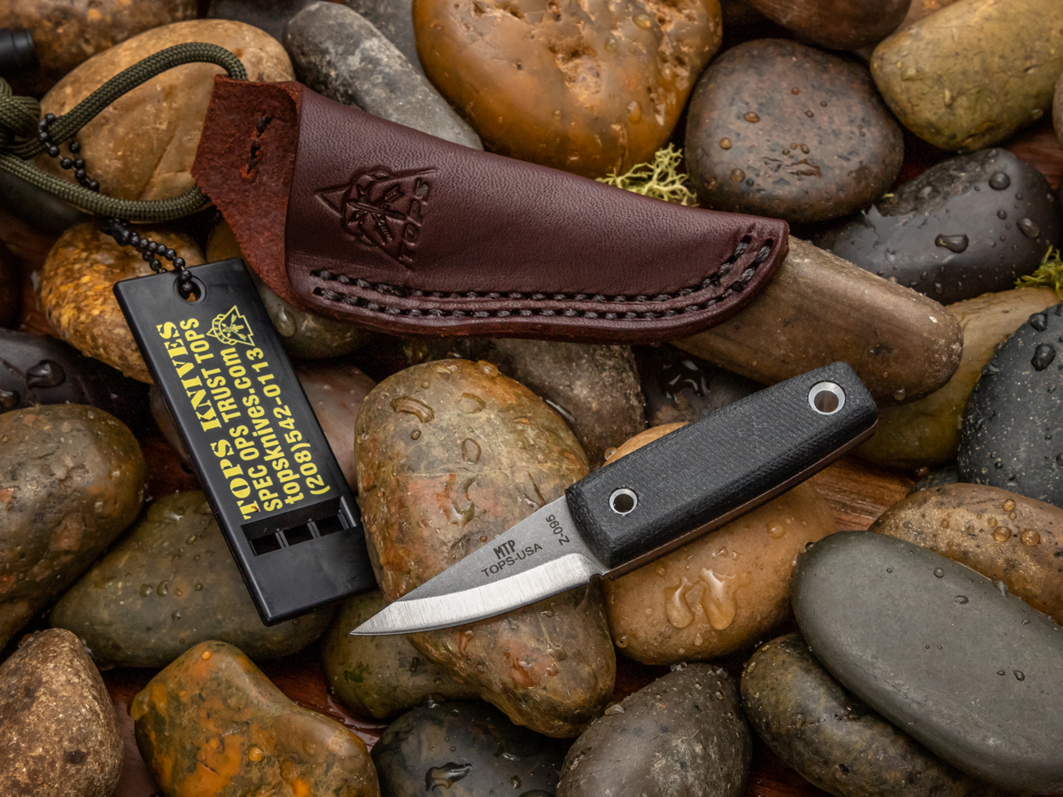 TOPS Mini Tanimboca Puukko sitting on wet rocks surrounded by sheath and survival whistle