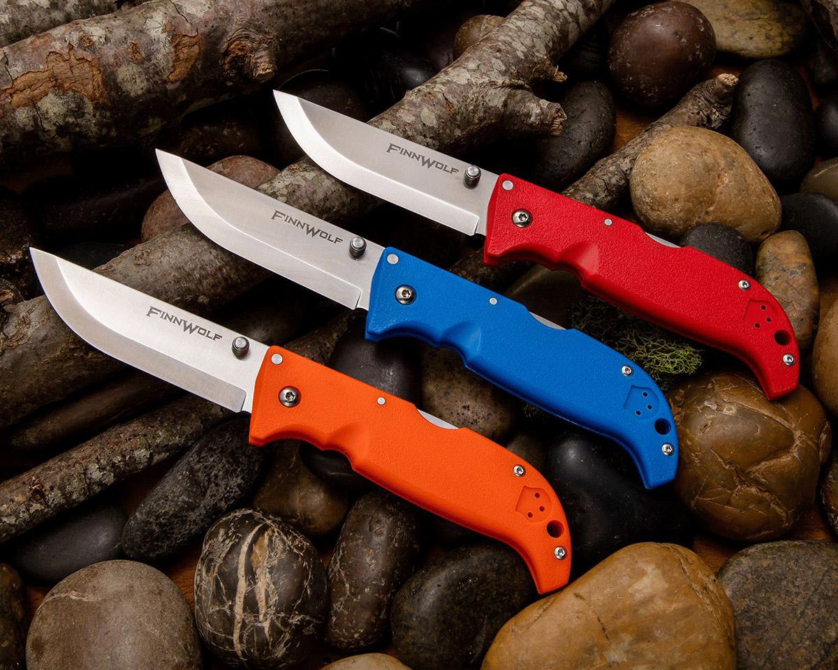 3 Cold Steel Finn Wolf Folders (orange, blue, & red) opened on rocks