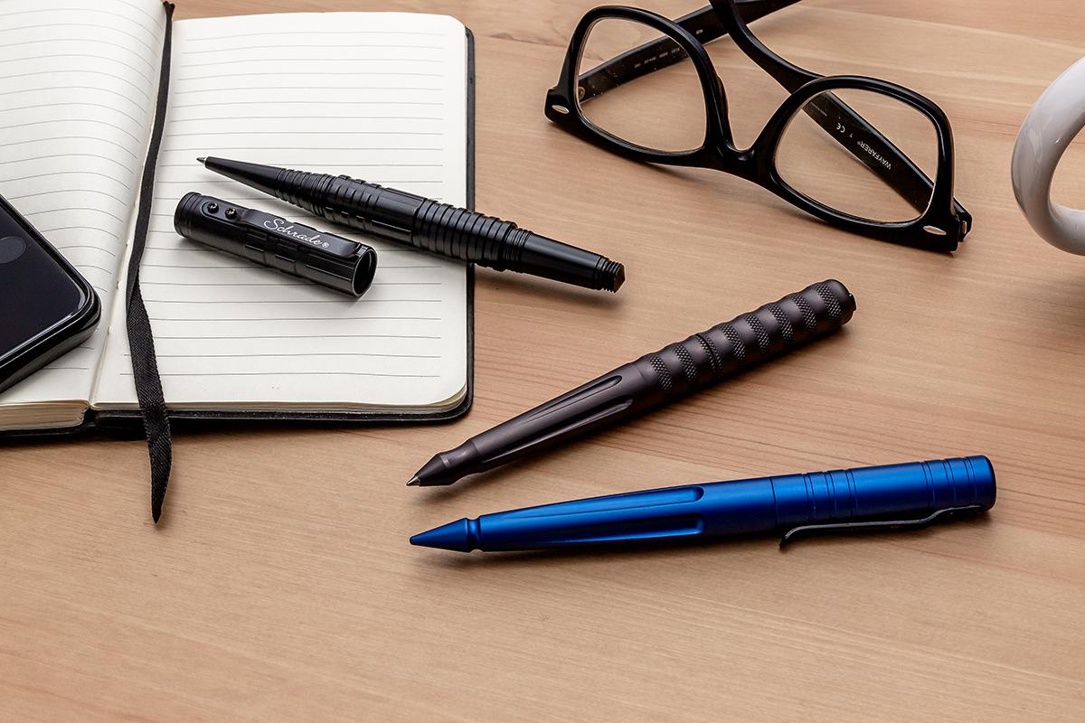 3 tactical pens sitting on an open journal